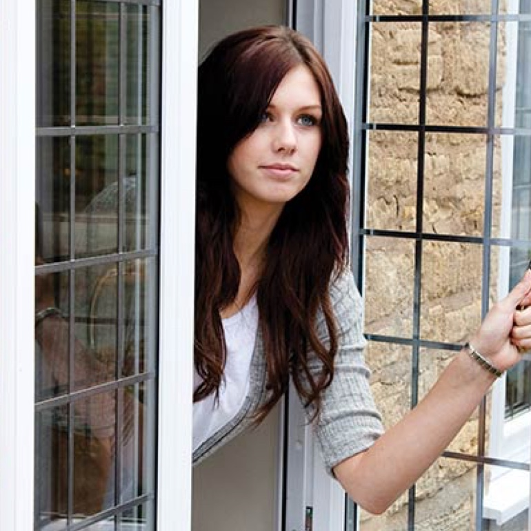 Woman looking outside a French Casement Window